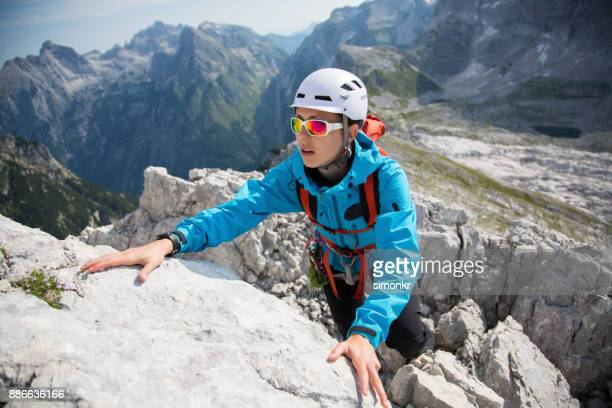 Young adult woman climbing on rock mountain