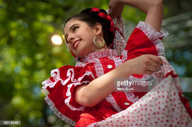 Young adult woman dancer in Latin/Spanish costume with arms raised, leaning back. Scarlet and white dress, green foliage behind her. RAW on file.