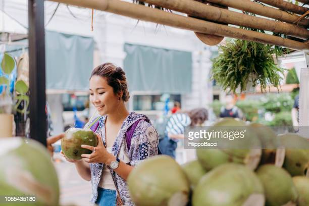 young adult woman drinking coconut water at the market - tropical fruit stock pictures, royalty-free photos & images