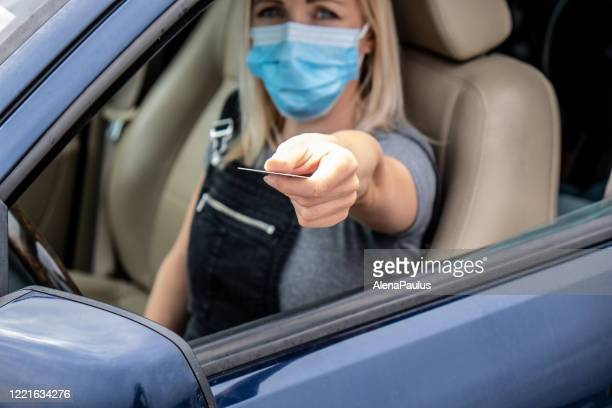 young adult woman driving a car and showing documents for covid-19 restrictions control - control stock pictures, royalty-free photos & images