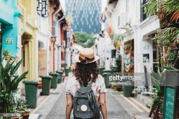 young adult woman exploring haji lane street in singapore - singapore stock pictures, royalty-free photos & images