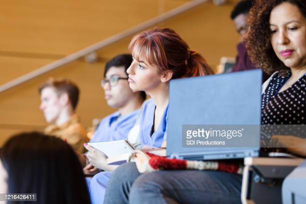 young adult woman focuses on lecture in college class - community college stock pictures, royalty-free photos & images