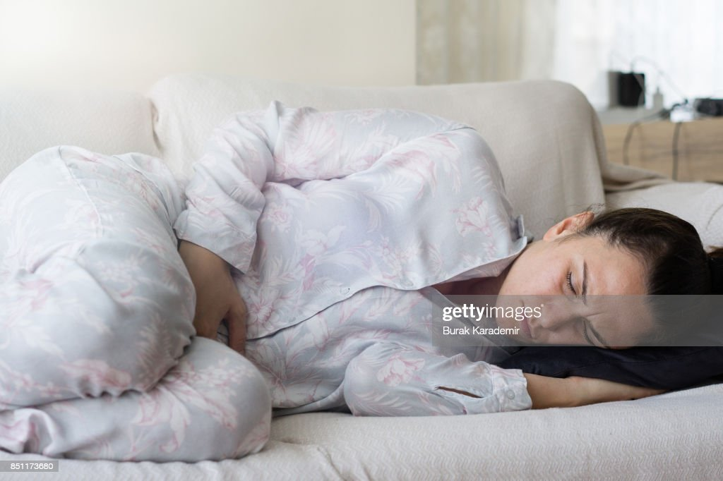 Young adult woman holding her crotch : Stock Photo