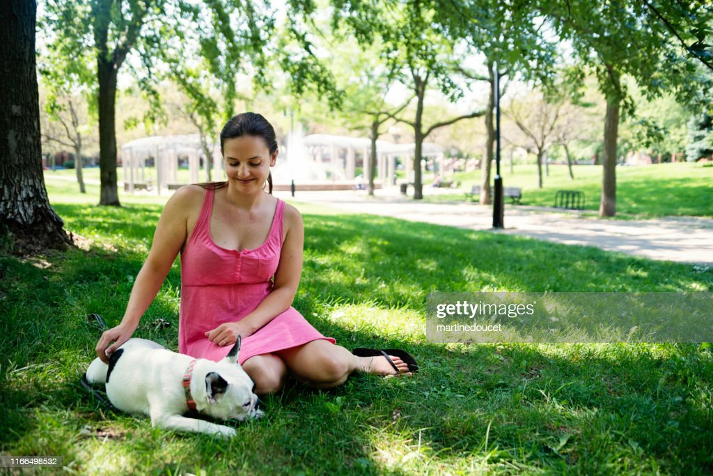 Young adult woman in a park with a french bulldog : Stock Photo