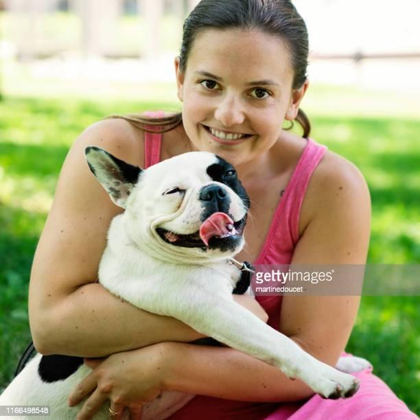 "mujer joven adulta en un parque con un bulldog francés - ""martine doucet"" or martinedoucet fotografías e imágenes de stock"