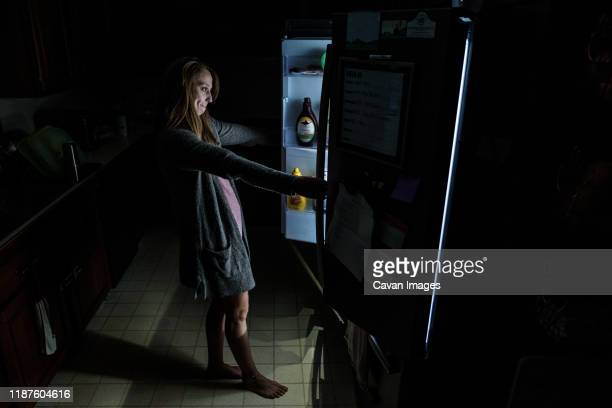 young adult woman in dark kitchen looks into open refrigerator - midnight stock pictures, royalty-free photos & images