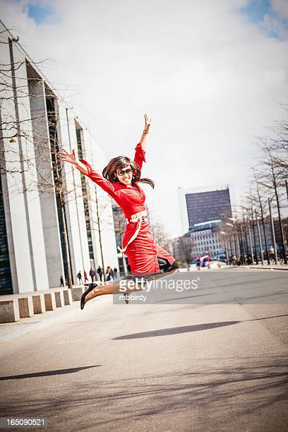 Young adult woman in red dress jumping
