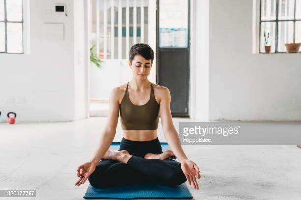 young adult woman is practicing yoga in a modern loft - yogi stock pictures, royalty-free photos & images