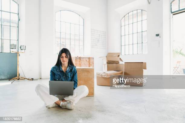 a young adult woman is working with her laptop in a new loft apartment - founder stock pictures, royalty-free photos & images