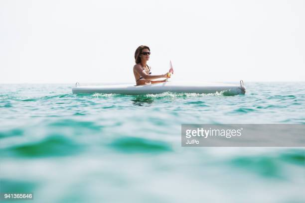 young adult woman kayaking - lagoon stock pictures, royalty-free photos & images