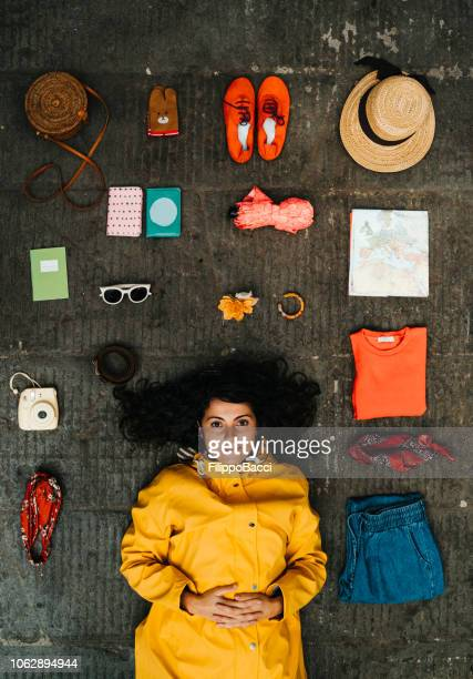 young adult woman lying down with clothes and various objects - knolling concept stock pictures, royalty-free photos & images