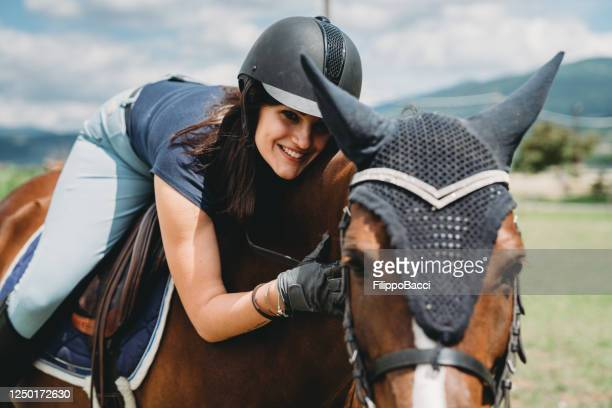 young adult woman lying on the back of a horse at the riding school - dressage stock pictures, royalty-free photos & images
