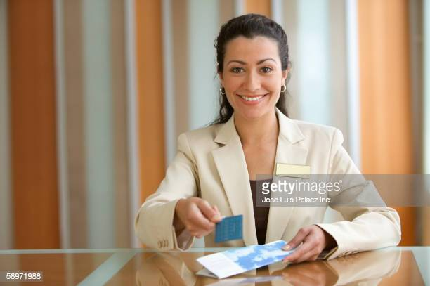 Young adult woman manager holding card