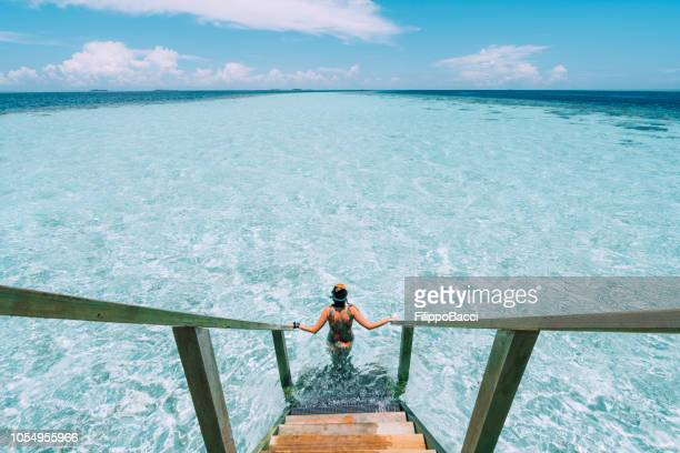 jeune femme adulte en descendant vers la mer - destination de voyage photos et images de collection