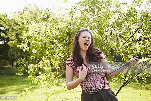 young adult woman playing air guitar with a badminton racket