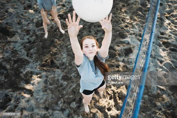 jonge volwassen vrouw buiten volleyballen - beachvolleybal stockfoto's en -beelden