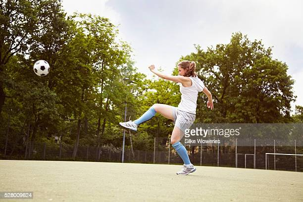 young adult woman playing soccer and kicking ball on sports field - patadas fotografías e imágenes de stock