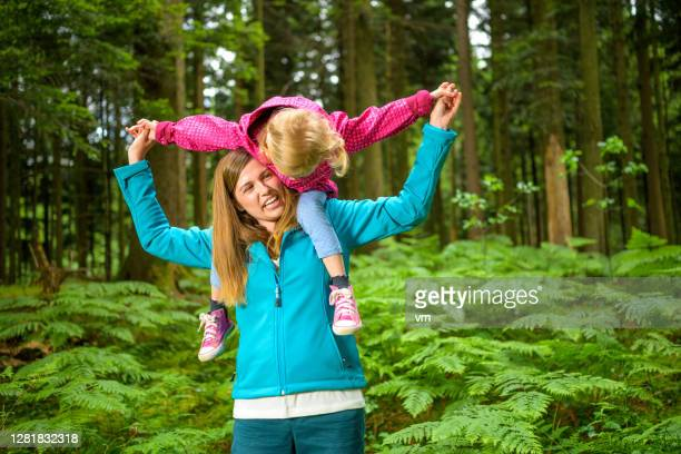 young adult woman playing with little child. - reality fernsehen stock pictures, royalty-free photos & images