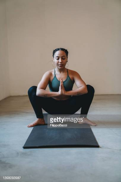young adult woman practicing yoga in garland position - yogi stock pictures, royalty-free photos & images