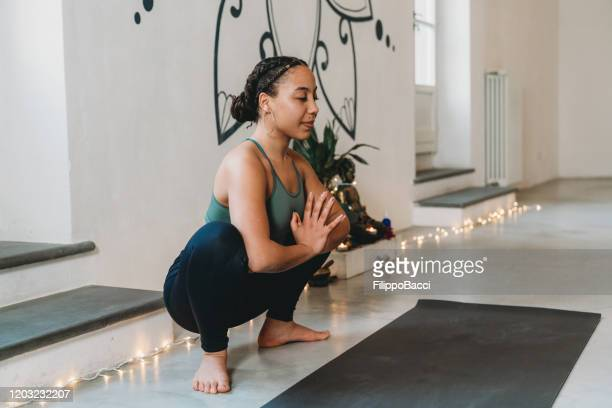 young adult woman practicing yoga in garland position - garland stock pictures, royalty-free photos & images