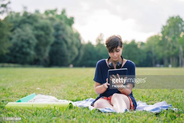 young adult woman reading an ebook at a public park - audio equipment stock pictures, royalty-free photos & images