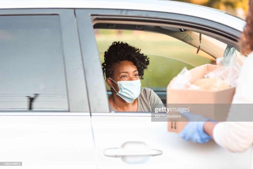 Young adult woman receives food during coronavirus epidemic : Stock Photo