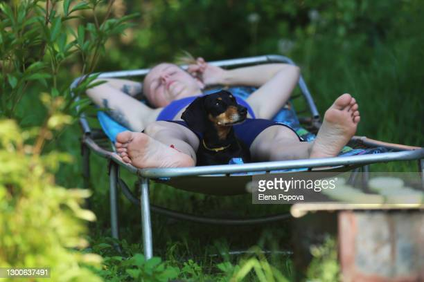 young adult woman relaxing at the garden with her black dachshund dog - sunbathing stock pictures, royalty-free photos & images