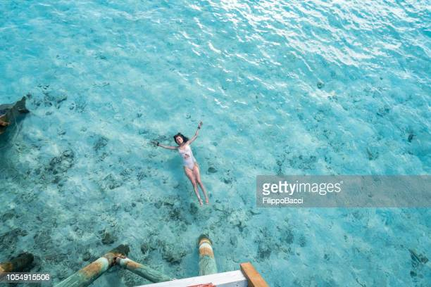 young adult woman relaxing in the sea - atoll stock pictures, royalty-free photos & images