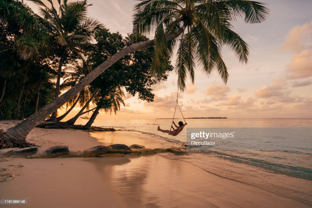 Young adult woman relaxing on a swing in a tropical paradise : Stock Photo