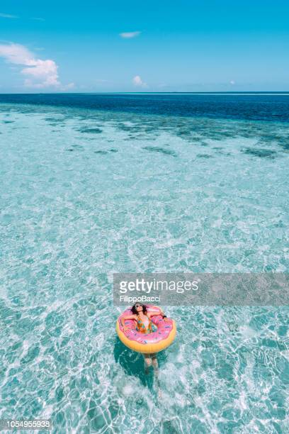 young adult woman relaxing on inflatable in the sea - inflatable ring stock pictures, royalty-free photos & images