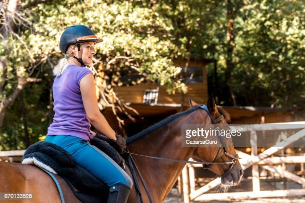 young adult woman riding a horse in pasture - rein stock pictures, royalty-free photos & images