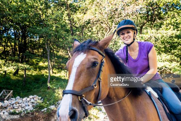 Young Adult Woman Riding A Horse In Pasture