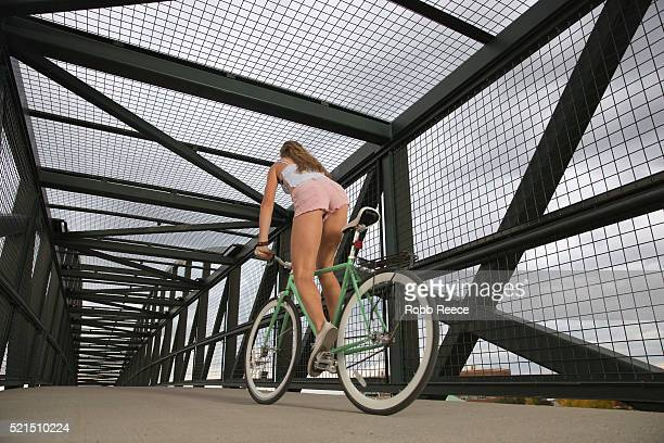 a young, adult woman riding her bicycle on an urban bridge for fitness - robb reece stock-fotos und bilder