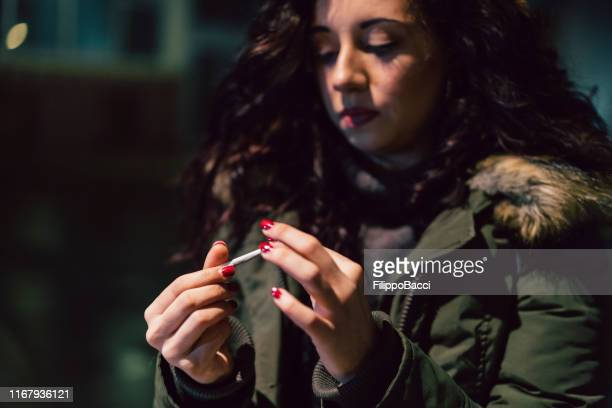 young adult woman rolling a cigarette outdoor in the city at night - one young woman only stock pictures, royalty-free photos & images