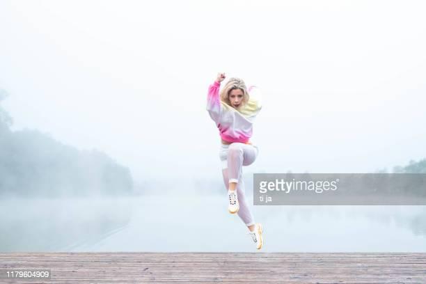 junge erwachsene frau läuft im freien in einem nebel stock foto - sportlerin stock-fotos und bilder