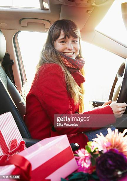 young adult woman sitting in a car with wrapped presents