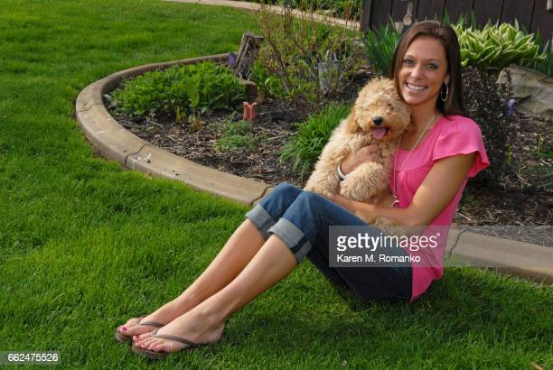 young adult woman sitting outside on grass holding a cockapoo puppy (6 mo) - cockapoo stock photos and pictures