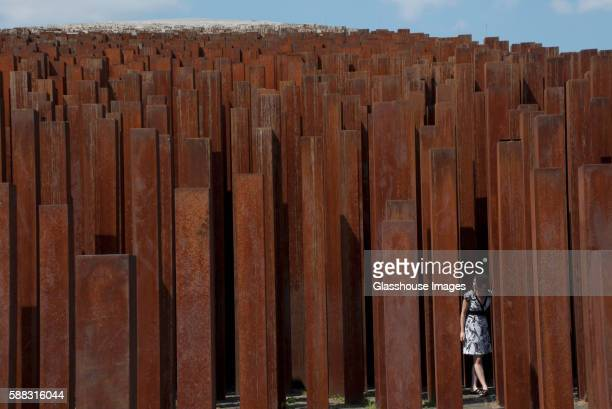 young adult woman, standing amongst rusted iron pillars - installation art stock pictures, royalty-free photos & images