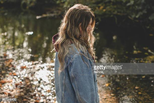 young adult woman standing by creek in denim jacket - denim jacket stock pictures, royalty-free photos & images