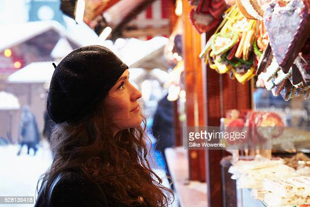 young adult woman standing in front of a booth of a christmas market