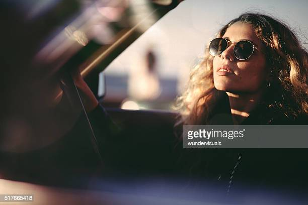 Young adult woman sunbathing in a convertible