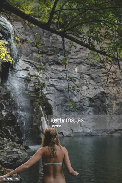 Young Adult Woman Swimming in Waterfall