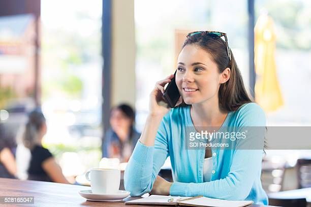 Young adult woman talking on cell phone in coffee shop