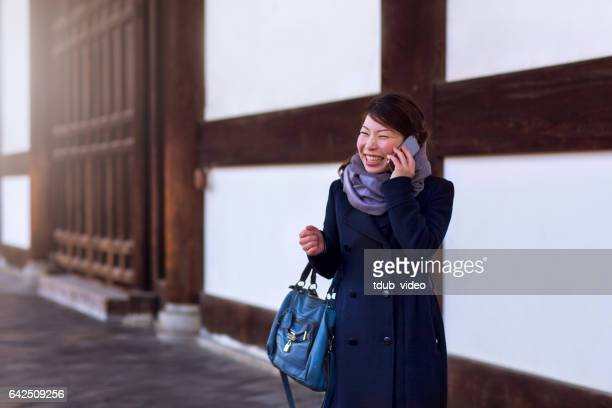 Young adult woman talking on the phone outdoors