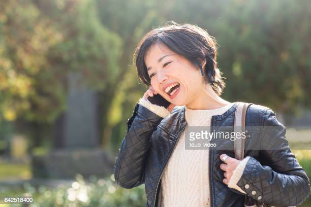 young adult woman talking on the phone outdoors - one mid adult woman only stock pictures, royalty-free photos & images