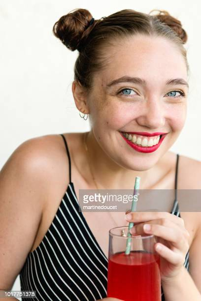 Young adult woman using paper straw.