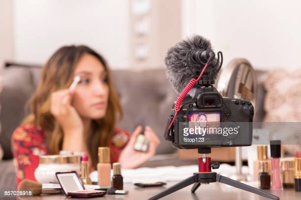 young adult woman vlogging about cosmetics, skin care products. - vlogging stock photos and pictures