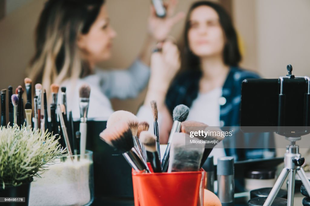 Young adult woman vlogging about cosmetics, skin care products. : Stock Photo