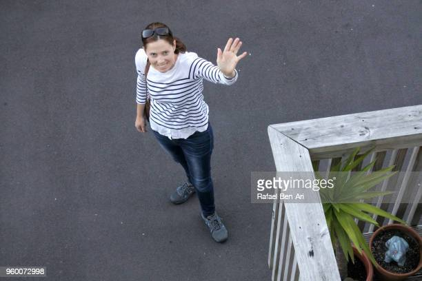 young adult woman waving goodbye before leaving home to work - rafael ben ari bildbanksfoton och bilder