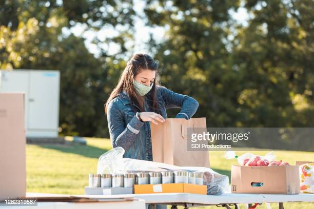 young adult woman wears mask while sorting donated food - giving tuesday stock pictures, royalty-free photos & images